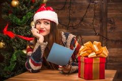 拿着一张新年和圣诞节明信片的美丽的女孩 免版税库存照片