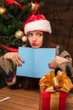 拿着一张新年和圣诞节明信片的美丽的女孩 库存照片