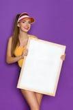 拿着一张白色图片的性感的妇女 免版税库存照片