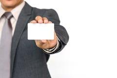 拿着一张白色空白的企业名称卡片的商人 免版税库存图片