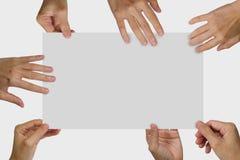 拿着一张白色空白的海报的许多手 库存图片