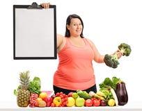 拿着一张空白的剪贴板和硬花甘蓝dumbbe的超重妇女 免版税库存图片