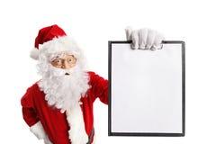 拿着一张空白的剪贴板的惊奇的圣诞老人 免版税库存图片