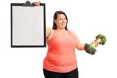 拿着一张空白的剪贴板和硬花甘蓝dumbbe的超重妇女 免版税图库摄影