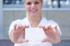 拿着一张空白的名片的年轻女实业家 库存照片