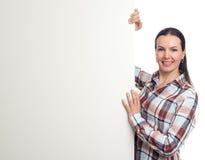 拿着一张空白的白色海报的深色的妇女 免版税库存照片