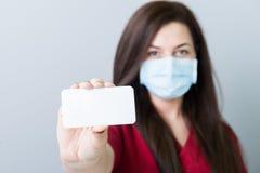 拿着一张空白的联络卡片或纸的女性医生 免版税库存照片