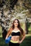 拿着一张蓝色瑜伽席子的美丽的妇女为锻炼做准备 一名成熟微笑的妇女的画象有健身席子的在公园 库存图片