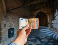 拿着一张被折叠的50欧元钞票的男性手 免版税库存照片
