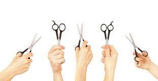 拿着一把剪刀剪的头发的手 免版税库存图片