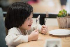 拿着一把匙子和叉子与的亚裔孩子 免版税库存图片
