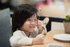 拿着一把匙子和叉子与的亚裔孩子 库存图片