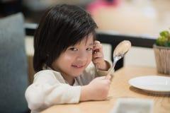拿着一把匙子和叉子与的亚裔孩子 免版税图库摄影