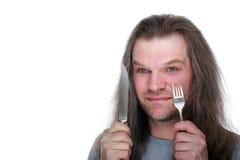 拿着一把叉子和刀子在他的手上的成人人,看somet 图库摄影