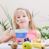 拿着一把叉子用巧克力涮制菜肴的美丽的小女孩 免版税库存照片