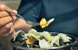 拿着一把叉子用淡菜的人的手 免版税库存照片