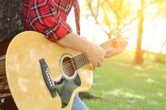 拿着一把声学吉他和演奏音乐的红色衬衣的年轻轻松的人在公园户外有阳光过滤器背景 免版税库存图片