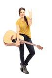 拿着一把声学吉他和给摇滚乐信号的女性 免版税库存照片