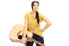 拿着一把声学吉他的女性音乐家 库存照片