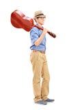 拿着一把声学吉他的年轻人 库存照片