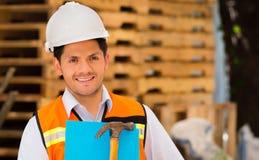 拿着一把文件夹和锤子在他的手上的微笑的年轻工程师在建造场所 库存照片