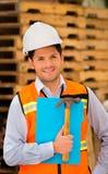 拿着一把文件夹和锤子在他的手上的微笑的年轻工程师在建造场所 免版税库存照片