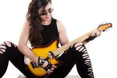 拿着一把电吉他的黑暗的皮革衣裳的美丽的女孩 免版税库存图片