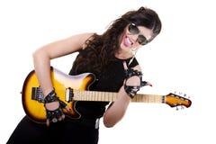 拿着一把电吉他的黑暗的皮革衣裳的美丽的女孩 免版税图库摄影