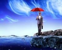 拿着一把红色伞的商人 免版税库存照片