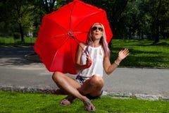 拿着一把红色伞的年轻白肤金发的运动妇女 图库摄影