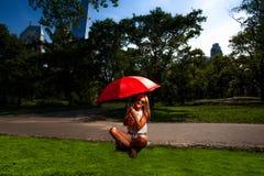 拿着一把红色伞的年轻白肤金发的运动妇女 免版税库存图片