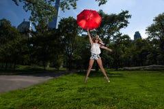 拿着一把红色伞的年轻白肤金发的运动妇女 库存照片