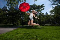 拿着一把红色伞的年轻白肤金发的运动妇女 免版税图库摄影
