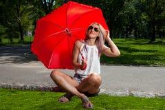 拿着一把红色伞的年轻白肤金发的运动妇女 免版税库存照片