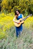 拿着一把经典吉他的可爱的年轻美女 免版税库存照片