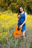 拿着一把经典吉他的可爱的年轻美女 库存照片