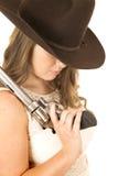 拿着一把更大的左轮手枪的女牛仔看下来 免版税库存照片