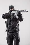 拿着一挺机枪在他的手上的恐怖分子瞄准隔绝在白色 免版税库存图片