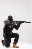 拿着一挺机枪在他的手上的恐怖分子瞄准隔绝在白色 库存照片