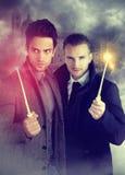 拿着一支不可思议的鞭子的两位年轻巫术师 免版税图库摄影
