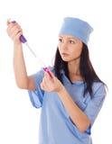 拿着一支剂量器分配器和管在她的手上的女性医生。 免版税库存图片