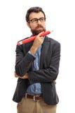 拿着一支大铅笔的沉思有胡子的人 免版税库存图片