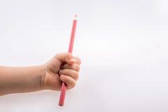 拿着一支桃红色颜色铅笔的手 库存照片