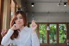 拿着一支笔和看在咖啡店的可爱的年轻亚裔女实业家画象在她的手上照相机与拷贝空间b 免版税库存照片