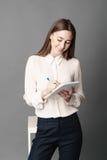 拿着一支笔记本和笔在她的手上的女实业家画象 一在灰色背景被隔绝 免版税库存图片