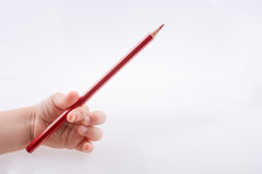 拿着一支红颜色铅笔的手 免版税库存照片