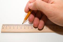 拿着一支铅笔在白色的人的右手 免版税库存照片