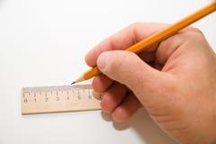 拿着一支铅笔在白色的人的右手 免版税库存图片