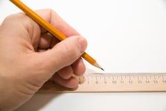 拿着一支铅笔在白色的人的左手 图库摄影