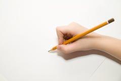 拿着一支铅笔在白色的孩子的右手 免版税库存照片